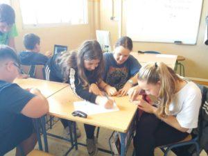 Alumnas y alumnos desgastando la cubierta de las semillas con papel de lija.